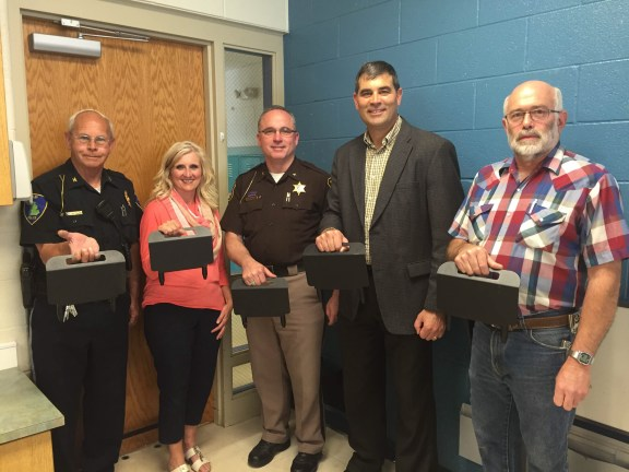 Displaying 'The Boot' security devices at Shelby Public Schools are, left to right, Shelby Police Chief Terry TenBrink, Early Childhood Center Coordinator Teresa Mead, Oceana County Sheriff Robert Farber, Shelby Public Schools Superintendent Dan Bauer and Shelby Public Schools Director of Maintenance Gary Stark.