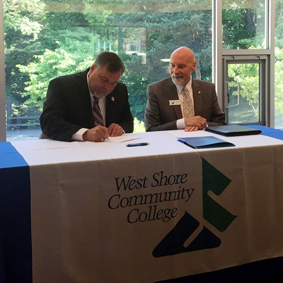 Dr. Randy Showerman of MSU signs the agreement while WSCC President Kenneth Urban watches.