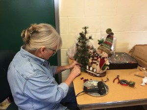Emilee Best puts the finishing touches on a holiday display.
