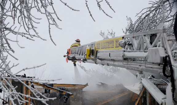 Firefighters from Mason County's Pere Marquette spray water on the wreckage Thursday afternoon.
