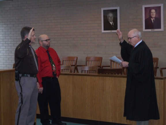 Judge Anthony A. Monton of the 27th Circuit Court swears in Craig Mast as the new Oceana County Sheriff. Standing next to Mast is Oceana County Prosecutor Joseph Bizon.