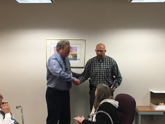 Det. Schneider receives a plaque for his 20 yeras of service from Oceana County Board of Commissioners Chairman Denny Powers.