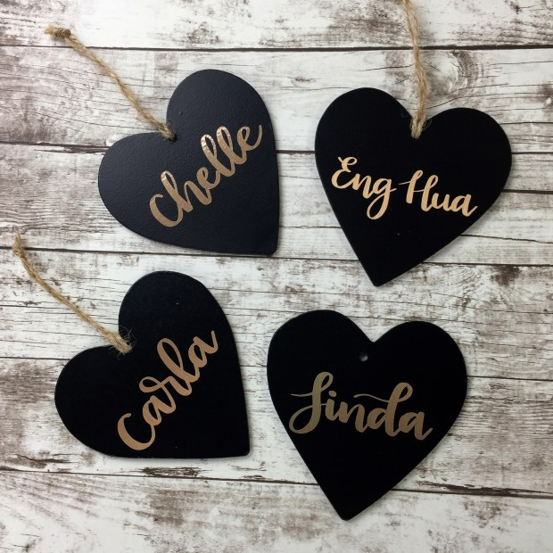 DIY wedding ideas: Name cards. We bought black hearts from Michaels (49¢ each) and customized them by adding our guests' names. We then attached the corresponding table assignments with ribbon, so they could be used later as ornaments. (photo by Chelle Perea/The Lemonade Store)