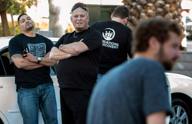 Gabe Chaves, left, and Jeff Dougherty, dubbed the Junkie Hunter, center, find addicts on the street like Timmy, foreground, to get them into rehab through their organization Foundations for Recovery. Today their patience grows thin as Timmy stalls to get high after saying he would let them drive him to a sober living home in Whittier. (Photo by Mindy Schauer, Orange County Register/SCNG)