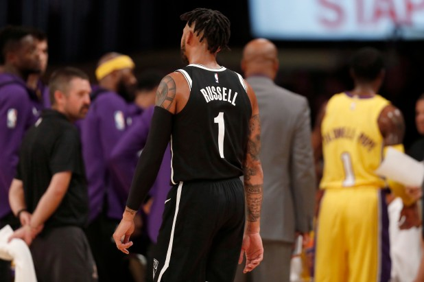Brooklyn Nets guard D'Angelo Russell, center, walks past the Los Angeles Lakers' huddle during the first half of an NBA basketball game, Friday, Nov. 3, 2017, in Los Angeles. (AP Photo/Ryan Kang)