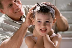 Close-up of a man shampooing his son's hair