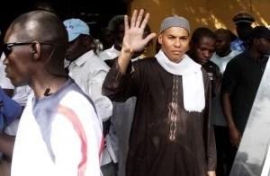 584741_karim-wade-fils-de-l-ancien-president-senegalais-abdoulaye-wade-fait-un-signe-de-la-main-pendant-son-arrestation-le-15-avril-2013-a-dakar