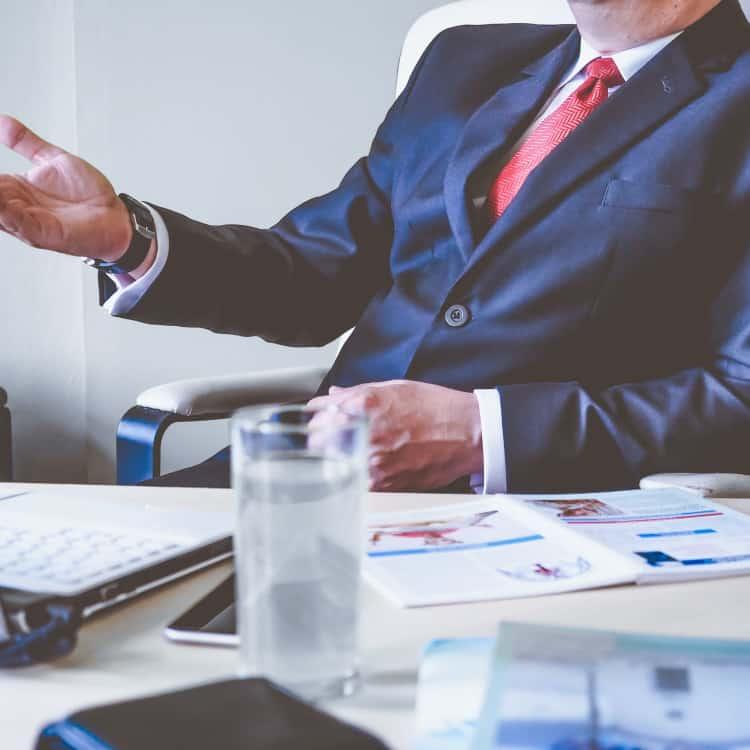 man in formal attire gesticulating at desk