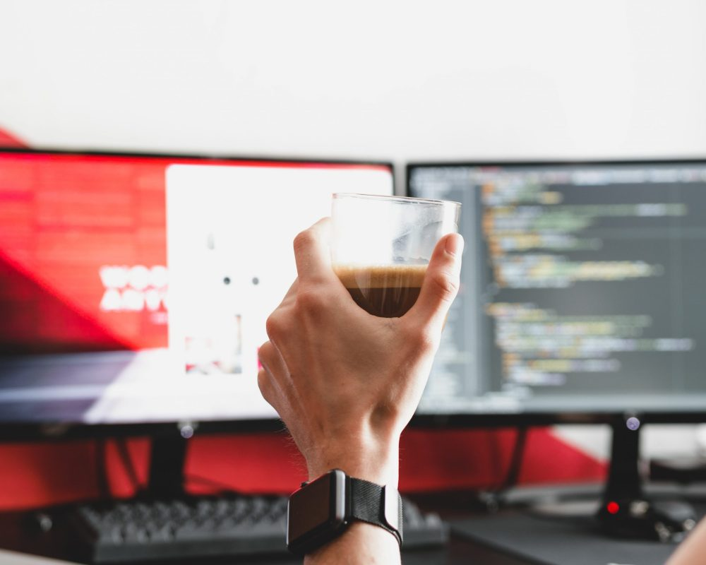 tech worker holding coffee in hand at computer