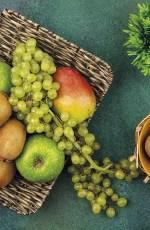 Panier contenant du raison, des kiwis, des pommes