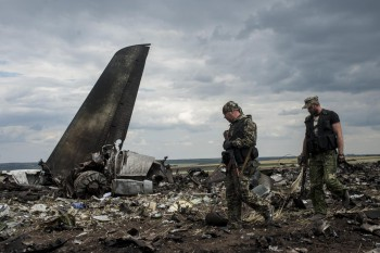 A pro-Russian fighter guards the site of remnants of a downed Ukrainian army aircraft Il-76 at the airport near Luhansk, Ukraine, Saturday, June 14, 2014 (Photo: Evgeniy Maloletka).