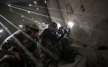 Syrian Rebel fighters belonging to the Javata Harria Sham Qatebee, watch over the enemy position during skirmishes at the first line of fire in Karmal Jabl neighborhood, district of Arkup, at the northeast of Aleppo Ctty, October 21, 2012 (Photo: Narciso Contreras / POLARIS).