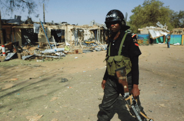 A police officer walks past shops destroyed in a suicide car bomb attack at the entrance to the Bompai police barracks near the police headquarters in the city of Kano. At least 185 people were killed during coordinated attacks by Boko Haram members on police facilities in the city on January 20, 2012.