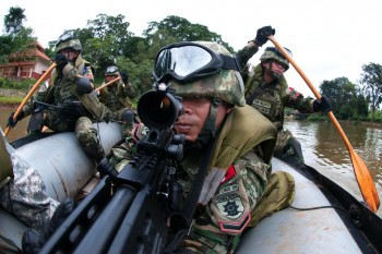 Indonesian army paratroopers use an inflatable raft to cross a waterway during a training raid on a high-value target as part of exercise Garuda Shield 2013 (bilateral training with the US) in Cilodong, Indonesia, June 12, 2013.