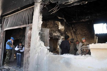 UN observers inspect a bombed-out school in the Syrian village of Tremsah, where as many as 200 people may have been killed in July 2012.