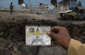 An Iraqi police officer holds up the identification card of a fellow officer who was killed when a car bomb exploded outside of the police station in Husseiniya, north of Baghdad (Photo: Teru Kuwayama/Corbis, 15 Dec 2003, Baghdad).
