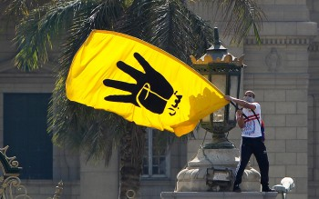 A student supporter of the Muslim Brotherhood and ousted Egyptian President Mohamed Mursi waves the yellow flag bearing the four-fingered Rabaa sign during a demonstration outside Cairo University May 14, 2014 (Photo: Mohamed Abd El Ghany / Reuters).