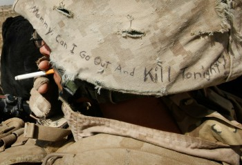 """Lyrics from a Misfits song, """"Mommy, Can I Go Out And Kill Tonight?"""" decorate the helmet of Marine Cpl. Jonathan Eckert of Oak Lawn, IL attached to India Battery, 3rd Battalion, 12th Marine Regiment while on patrol near Forward Operating Base (FOB) Zeebrugge on October 15, 2010 in Kajaki, Afghanistan. The Marines of India Battery, 3rd Battalion, 12th Marine Regiment are responsible for securing the area near the Kajaki Dam on the Helmand River (Pfoto: Scott Olson / Getty Images)."""