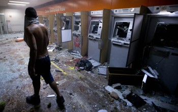 Brazil is facing a social and economic crisis. On the photo, a protester looks at vandalized cash machines at a bank during a demonstration in Rio de Janeiro, Brazil, Monday, June 17, 2013.
