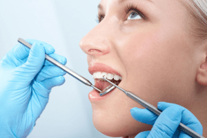 patient with manual scaling instruments in mouth