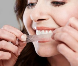 close up of woman using white strips