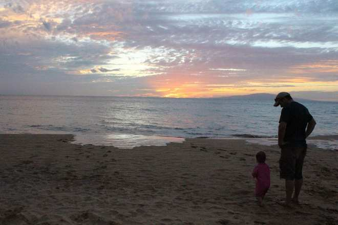 Father and daughter watching the sunset during our Maui family vacation.