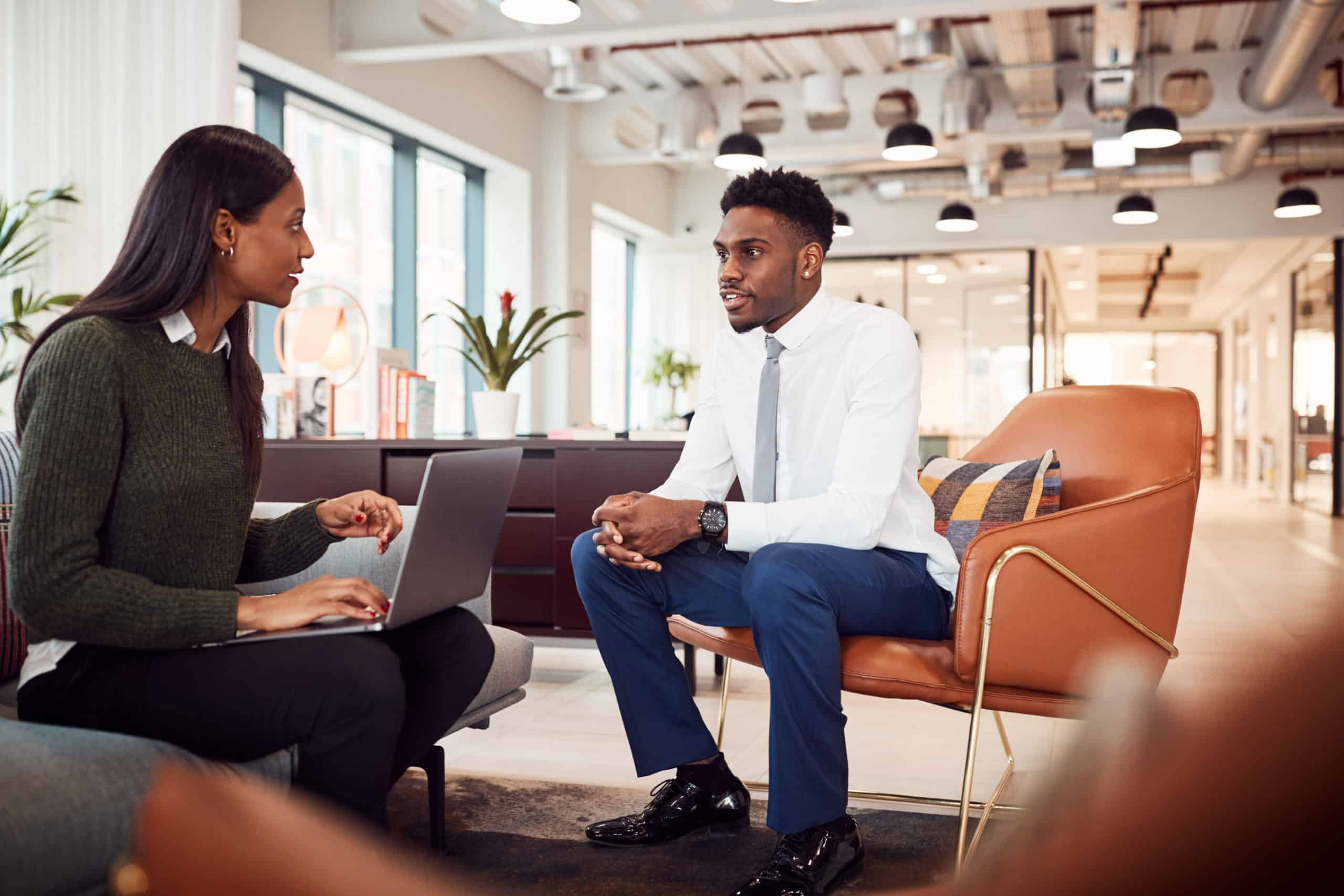 Person with computer talking with a person dressed for an interview
