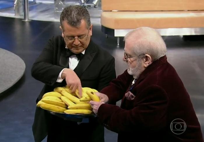 Jô leva um cacho de bananas e distribui para a plateia