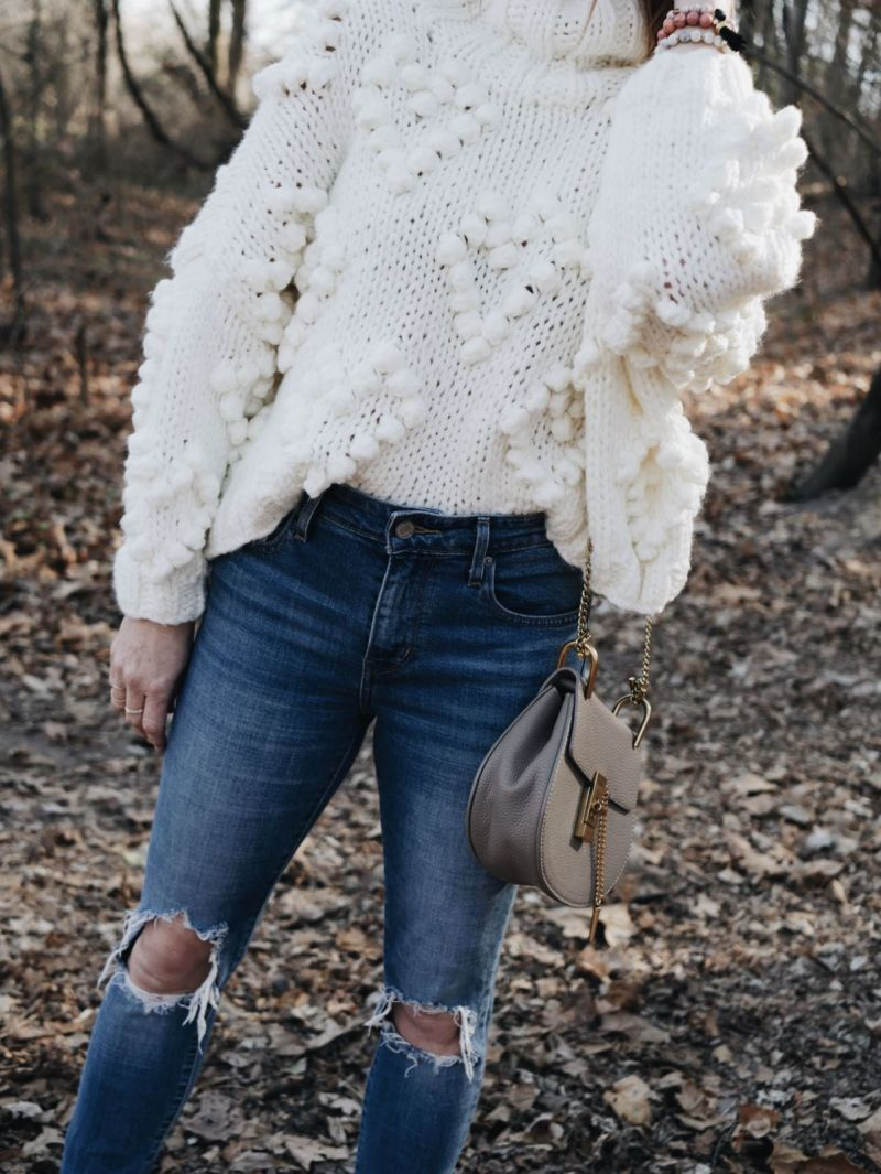 White Turtleneck Pom Pom Sweater with ripped jeans