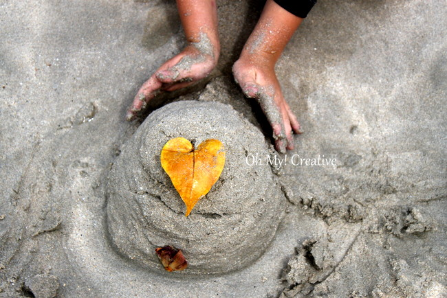 Sand castle on the beach with child's hands - love