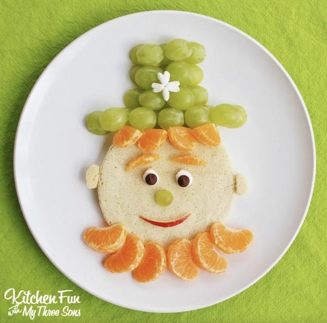 Cute leprechaun pancakes made with grapes and tangerines for decoration..