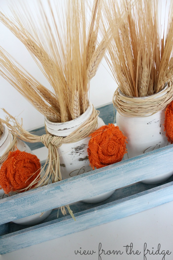 These Fall Easy Mason Jar Centerpieces are a perfect Fall decor accent for the home. Use it to decorate the table, fireplace mantel or as fall front porch decor! The distressed mason jars are accented with easy to make burlap rosettes! OHMY-CREATIVE.COM