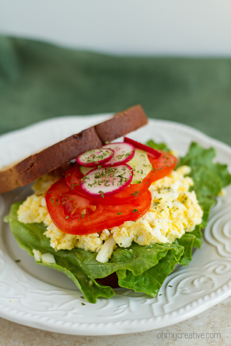 An egg salad sandwich with tomatoes and lettuce