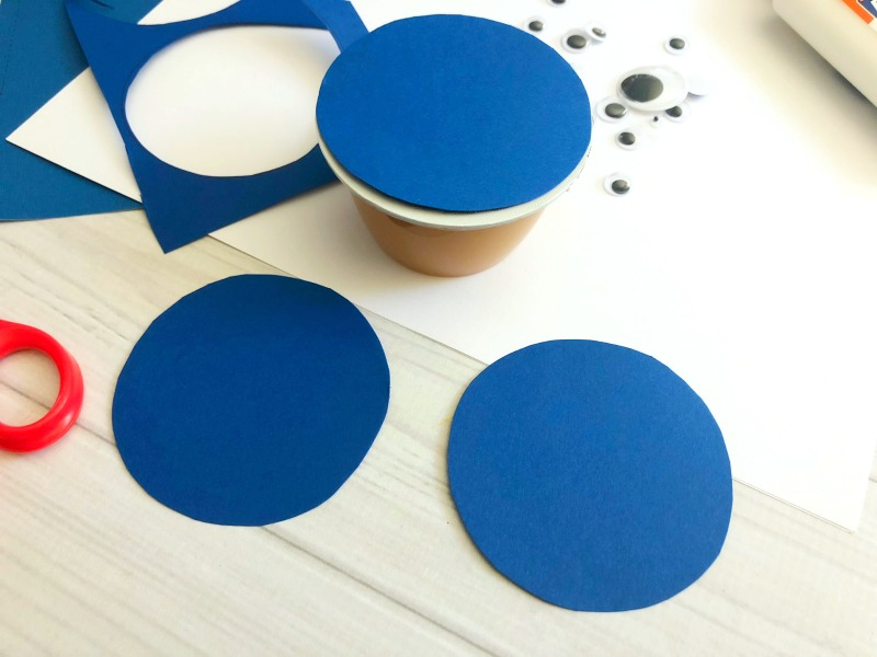 Trace blue paper and cut out circles to make sharks for the applesauce cups.