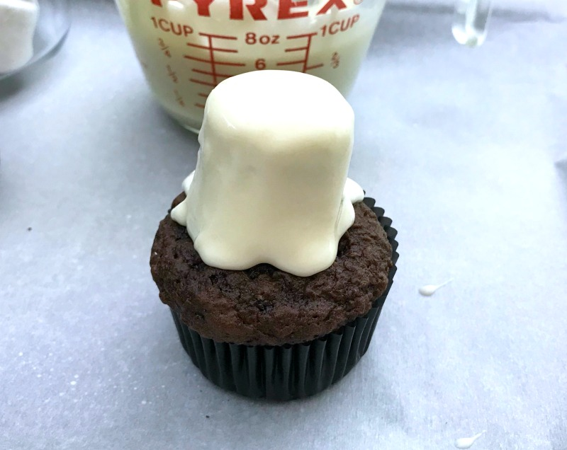 Assembling top of ghost cupcakes for halloween party. These Marshmallow Ghost cupcakes for Halloween are an EASY semi-homemade treat! OHMY-CREATIVE.COM | #marshmallowghostcupcakes #ghostcupcakes #ghost #halloweentreat #halloweendessert #halloween