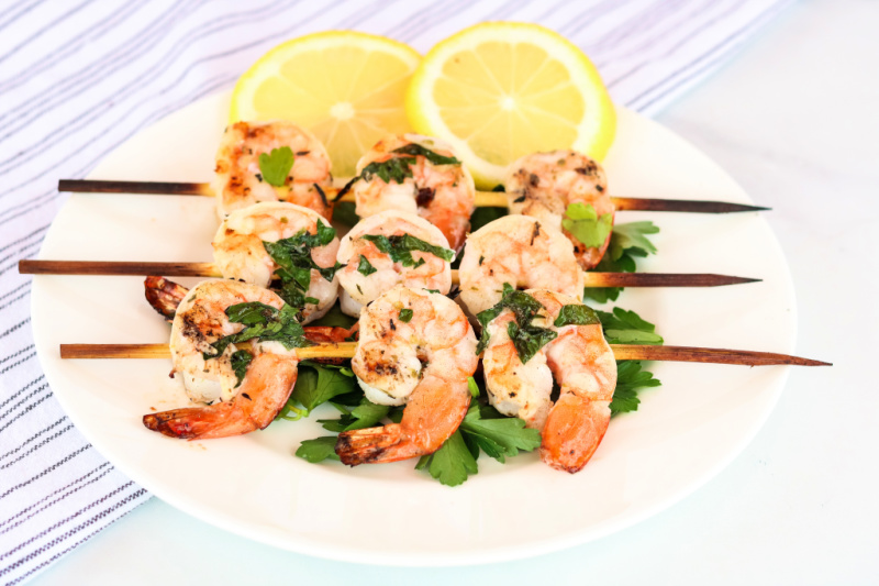 plate of lemon garlic grilled shrimp garnished with Fresh parsley and lemons