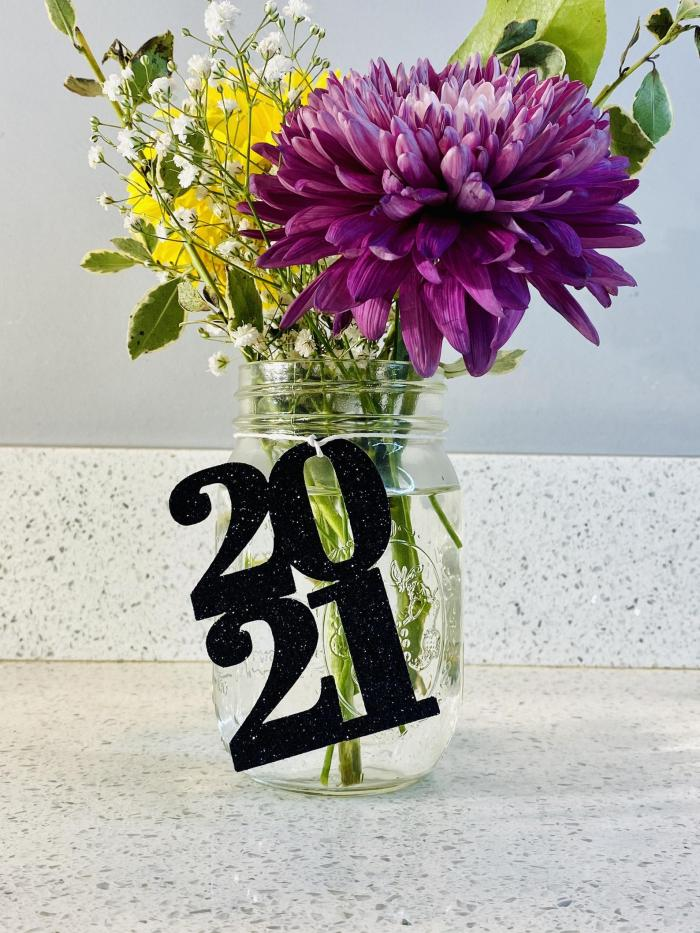 Mason jar filled with colorful flowers and a black 2021 cutout tied onto the mason jar to created a pretty table centerpiece.