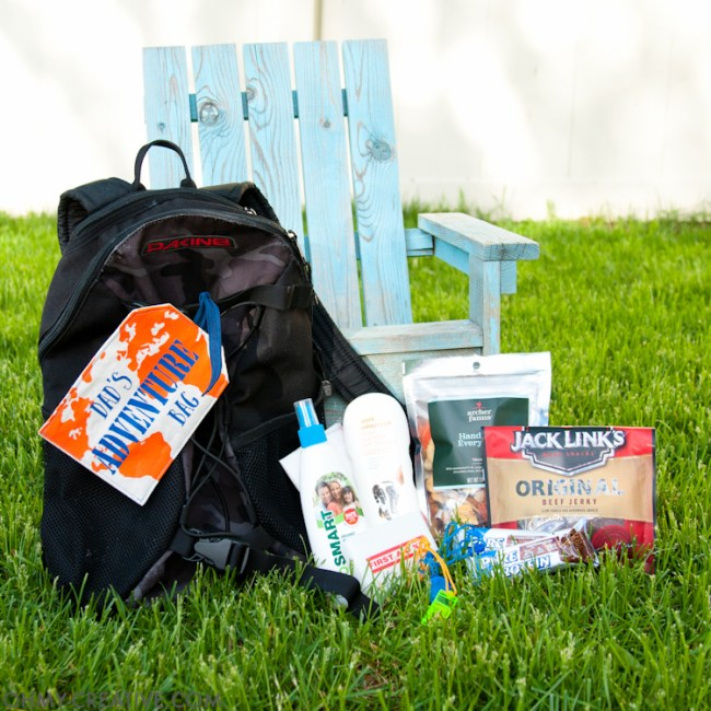Backpack filled with helpful travel items and adorned with a Father's Day printable tag