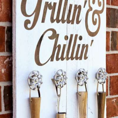 White wooden board made with knobs to hang grilling utensils on