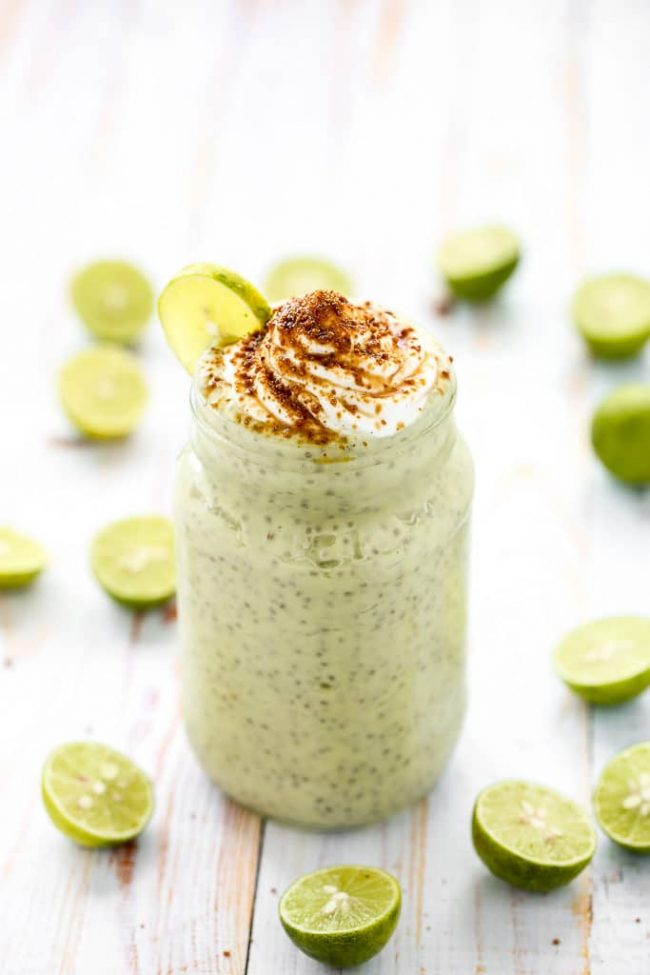 Key lime pie chia pudding on a white wooden background with slices of lime around the pudding.