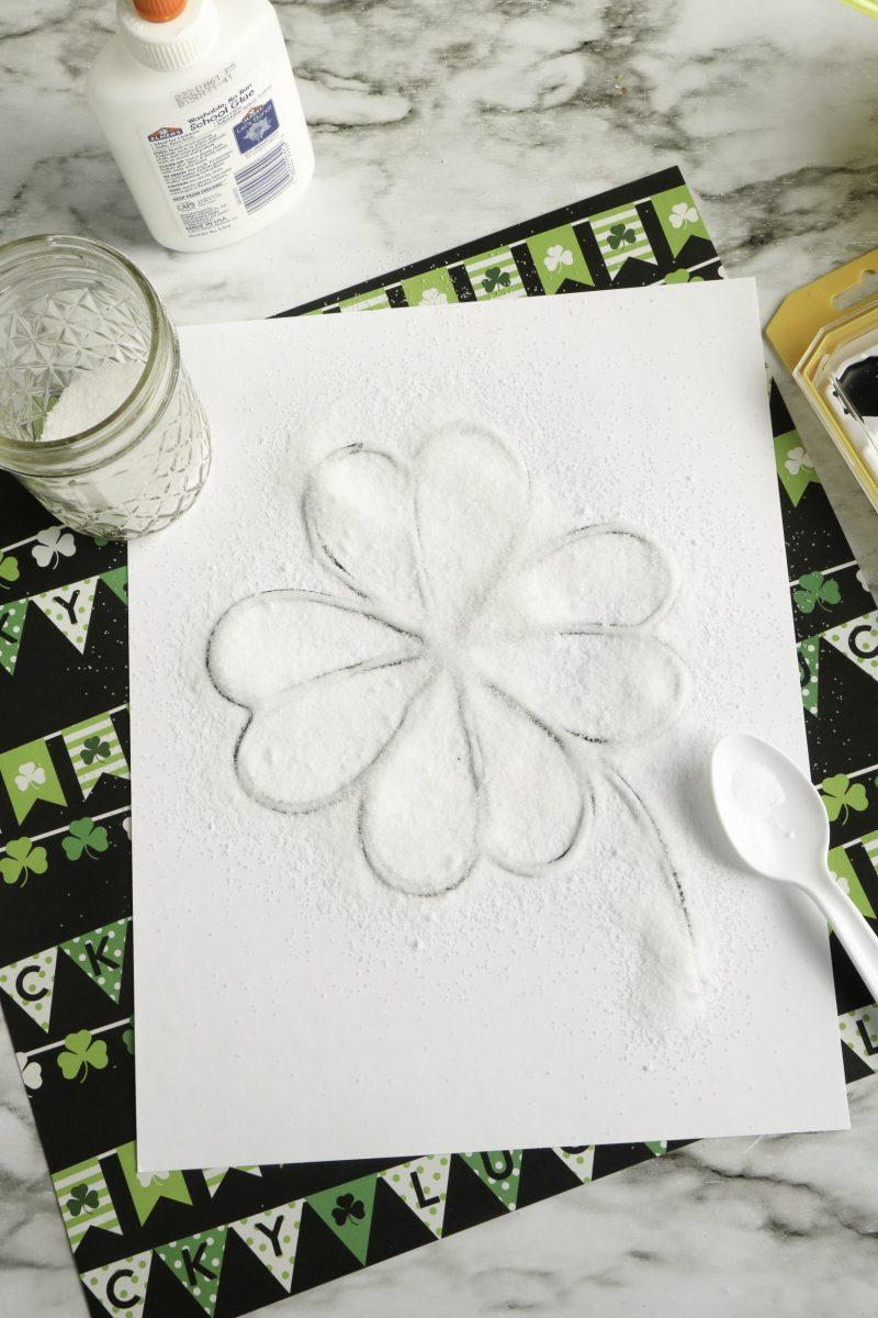 While glue is still wet, sprinkle the shamrock with salt. Shake off excess salt.