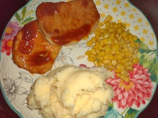 [;ate of glazed pork chops meal with corn and mashed potatoes