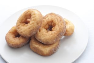 Homemade ring doughnuts made from fried dough served on a white porcelain plate, close up with copy space