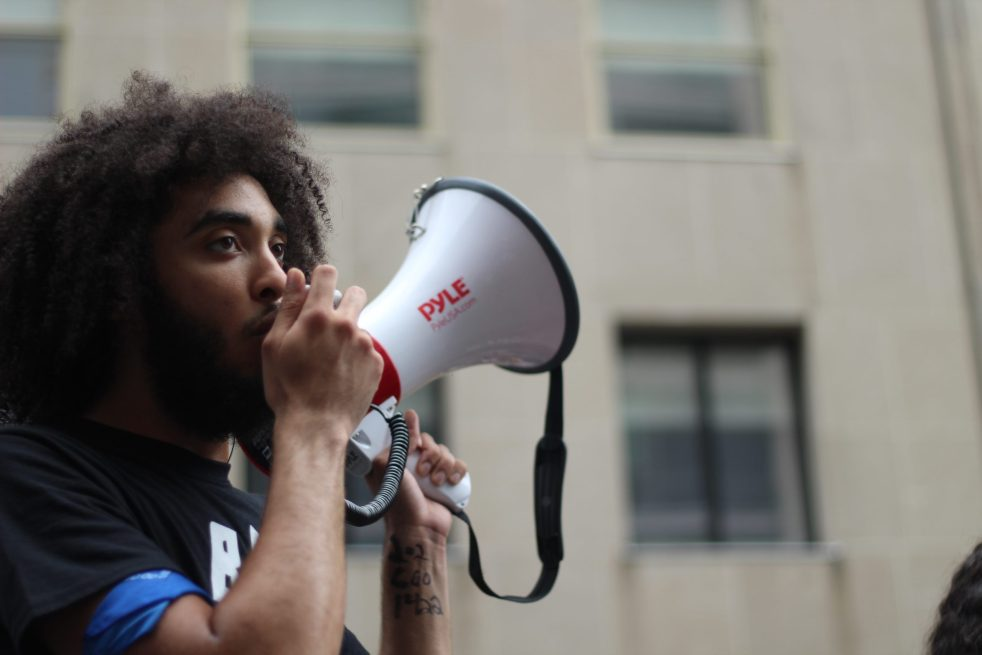 Photo: A Black person with long curly hair shouts into a bullhorn at a counter-protest to a fascist event in Washington, D.C.