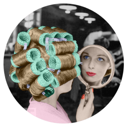 A lady with her hair in curlers looks into a mirror
