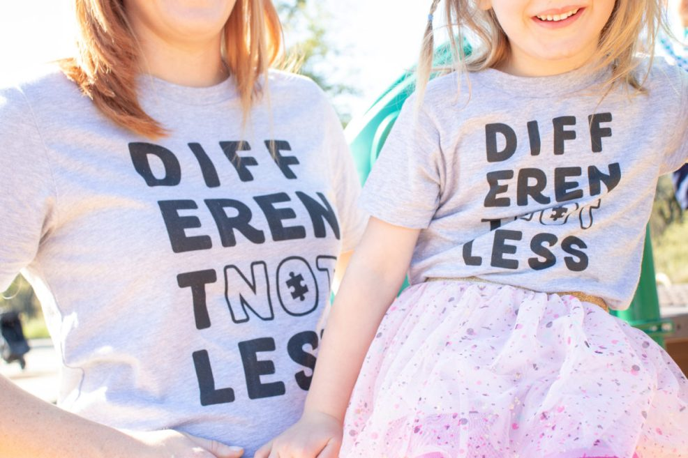 """close up of shirts that read """"Different Not Less"""""""