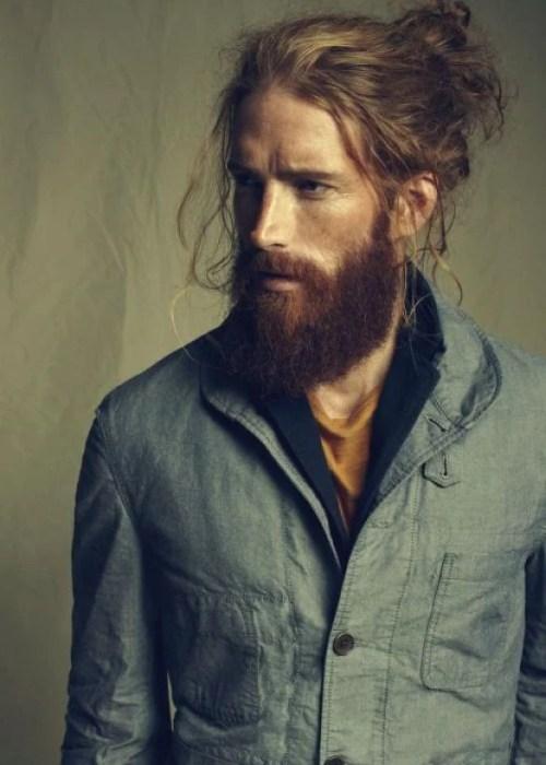 Hombre rubio con barba y cabello largo agarrado