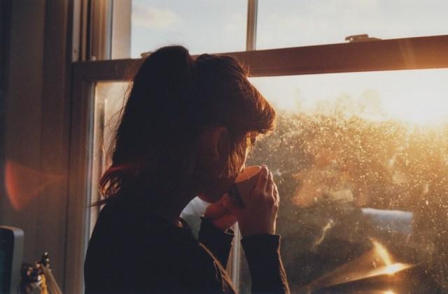 Mujer tomando una taza de café mientras observa por la ventana