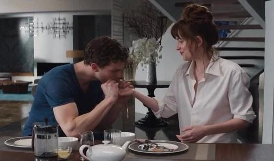 personas compartiendo el desayuno mientras él le besa la mano