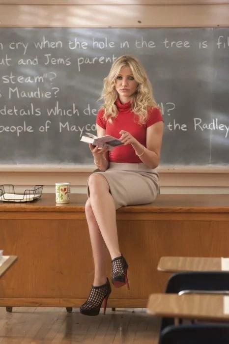 actriz cameron diaz sentada en un escritorio leyendo un libro